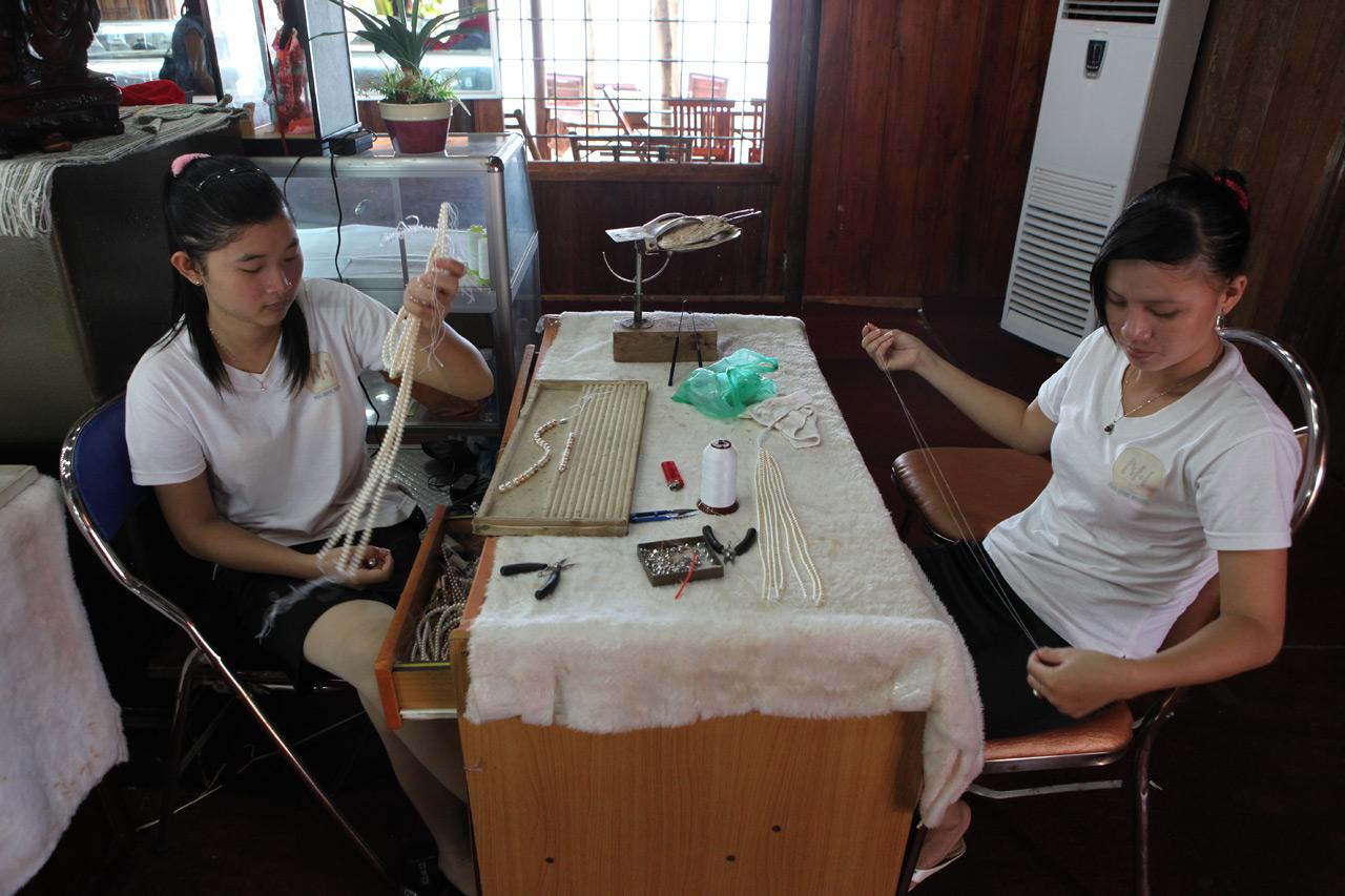 Вьетнамские девчонки насаживают жемчужные бусы